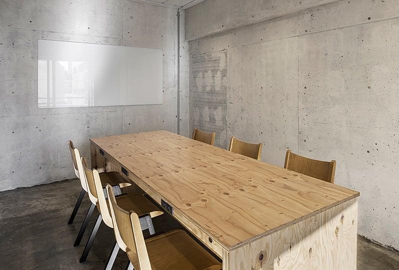 無機質なコンクリートの壁面と木製の家具がマッチします。(55インチモニター付) - HOLDER jingumae6 4階会議室の室内の写真