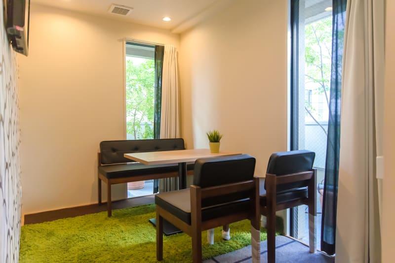 自然光が2方向から差し込み、緑が見えて心地いい空間。 - Feel Osaka Yu 【超高速WiFi】緑見える会議室の室内の写真