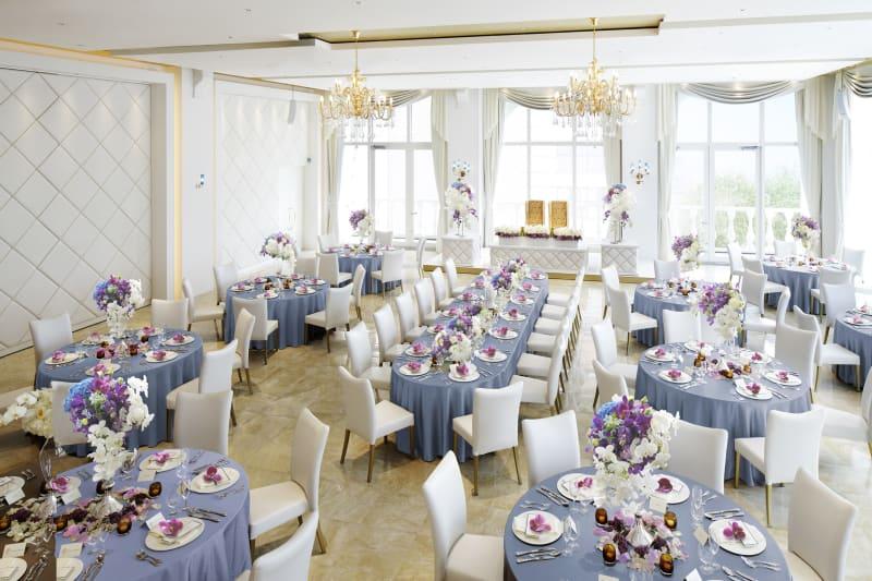 サファイアの輝きをイメージした「AZZURRO(アッズーロ)」。白を基調にした空間に自然光があふれる、明るく華やかなバンケットです。 - カノビアーノ福岡 アズーロ(パーティー会場)の室内の写真