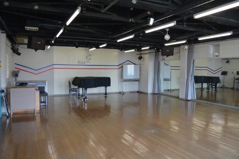 グランドピアノ・エレクトーン・PA完備、床もダンスやバレエに最適なクッションのある木製床、客席は120席まで収容可能 - ヤマハウイング北勢堂ビル内 多目的スペース ホールの室内の写真