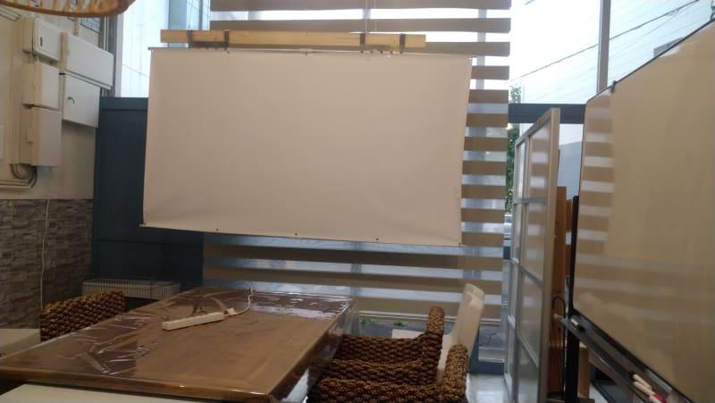 プロジェクタースクリーンと大きなホワイトボード。人が通るオープンスペースです。 - レンタルスペース夕顔瀬 男性も利用可。全体貸し出しの室内の写真