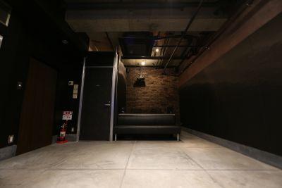 モニタの対面側には、23人掛けのソファと、その奧にワーキングデスクがあります。ライブ配信や編集の際の技術者席として。 - 渋谷クリエイティブスタジオ STUDIOの室内の写真