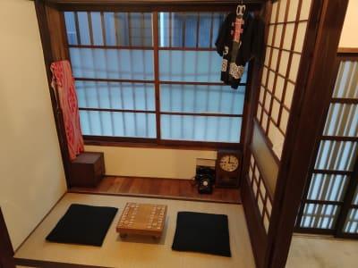 一階:和室。ちゃぶ台の代わりに将棋盤(オプション)を配置。窓を開ければ換気も可能で、道行く人を眺めながら対局をお楽しみ頂けます。 - 月島長屋 多目的スペースの室内の写真