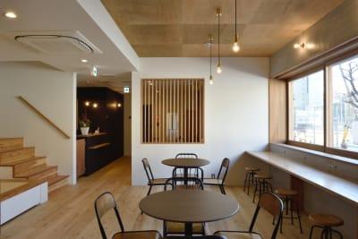 共用スペースのフローリング部分には机2台とカウンター、椅子が12脚あります - みつわ屋 共用スペースの室内の写真