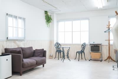 自然光の入る窓の近くには、ソファーやガーデンテーブル&チェア、空気清浄機などが有 - スタジオフェアリー 天満橋店 ガーデン スタジオの室内の写真