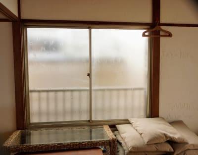 北側には隣家が迫っており、眺望は望めません。左側の窓ガラスにヒビが入っており、透明なテープで留めています。 - 子育てカフェeatoco 2階和室の室内の写真