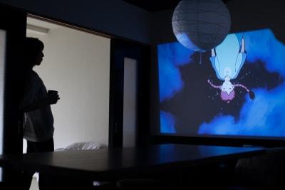 リビングの壁にプロジェクターでDVDなどを映すことができます。 - Nishichaya旅音 リビングの室内の写真