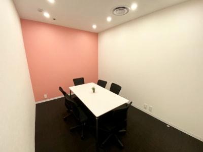 ピンクのアクセントカラーがおしゃれな個室です。ミーティングや勉強会の他、フリーWi-Fiを完備しておりますのでWEB会議にも最適です。 - シェアオフィスURL 個室(ピンク)の室内の写真