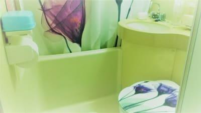 トイレは3点セットです。バスカーテンやマットなどは美しい紫の花のイメージ。香りにも配慮しています。オイルなどを流したいお客様にはバスルームのシャワーもご利用いただけます。 - ヒーリングルーム横浜駅西口鶴屋町 ヒーリングルーム横浜鶴屋町の室内の写真