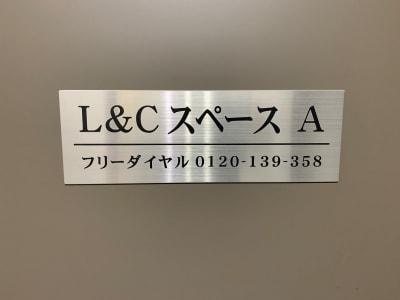 扉に看板を掲げています。ドアノブにキーボックスがあります。 - L&Cスペース日本橋駅前 A号室の入口の写真