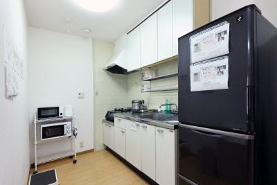 キッチンです。グリル、流し台、オーブントースター、電子レンジ、冷蔵庫が揃っています。 - 名古屋の部屋 グリーンスペース名古屋の室内の写真