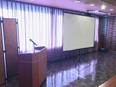 プロジェクタースクリーンと司会台。ワイヤレスマイク2本。 - 石原ビル レンタルスペース 貸し会議室の設備の写真