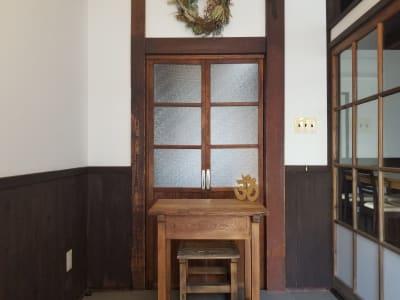 エントランスは4.6㎡(畳約3畳分)あり、広々とした空間です。木製のテーブルとイスを使って受付も可能です。 - 癒しの古民家Kyoto Knot レンタルスタジオの入口の写真
