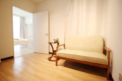 待合スペースにソファと小さなテーブルあり。 - レンタルサロンBeeの室内の写真