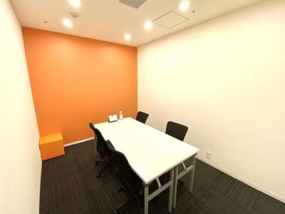 オレンジのアクセントカラーがおしゃれな個室です。ミーティングや勉強会の他、フリーWi-Fiを完備しておりますのでWEB会議にも最適です。 - シェアオフィスURL 個室(オレンジ)の室内の写真