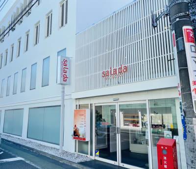 白壁に赤サインが目印 - サラダ自由が丘本店 サロンスペース、個室タイプの外観の写真