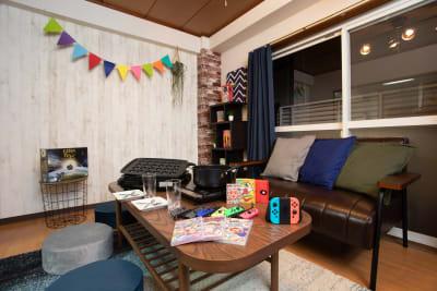 テレビ逆側の壁はインスタ映えしやすいウッドスタイルでおしゃれに演出! - ポップルームなんば ボードゲーム充実のくつろぎ空間の室内の写真