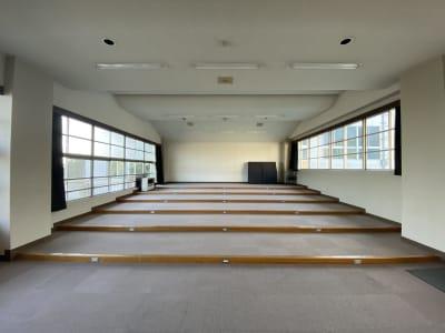 うしろの壁面全体をスクリーンとして使うこともできます。 - 八ヶ岳コモンズ シアターコモンズ(音楽教室)の室内の写真