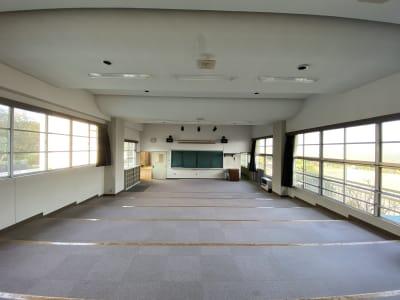 階段上の床と音楽室特有の天井の形状です。正面に黒板とスクリーンがあります。 - 八ヶ岳コモンズ シアターコモンズ(音楽教室)の室内の写真
