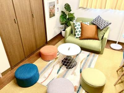 二人掛けソファとクッションスツール、テーブル - としょかんのうら・かしわ 柏レンタルスペース・貸し会議室の室内の写真