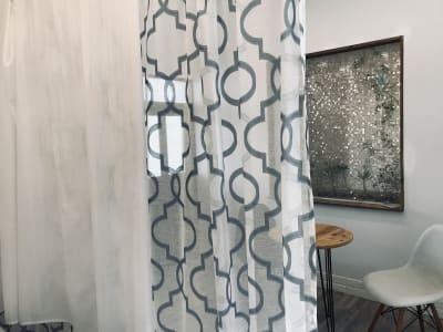 スペースを2分するようにカーテンを設置しています。圧迫感の少ない透ける素材ですが、2枚重ねて使う事で着替え時の目隠しとしても使えます。 - レンタルサロン アイリー 完全個室タイプの室内の写真