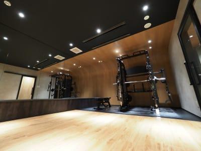 長辺は鏡張りでフォームチェックもばっちり - パーソナルジムMOGAR トレーニングジムの室内の写真