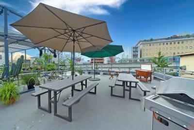 パラソル付きテーブル(6名掛け)×2は無料でお使い頂けます。 ※レイアウトは若干変更になる可能性があります。 - KLASI COLLEGE 屋上プライベートBBQスペース①の室内の写真