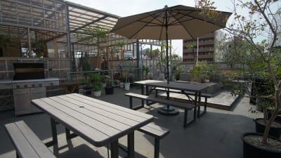 パラソル付きの6名掛けテーブル×2(パラソルは2本ございます。) - KLASI COLLEGE 屋上プライベートBBQスペース②の設備の写真
