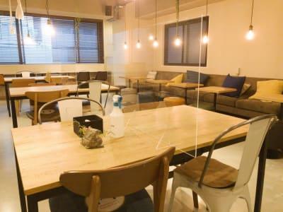 各テーブルには飛沫防止用パネルを設置、椅子は対面での配置を避け定期的に館内消毒も行っております。 - THE STAY OSAKA コワーキング・多目的スペースの室内の写真