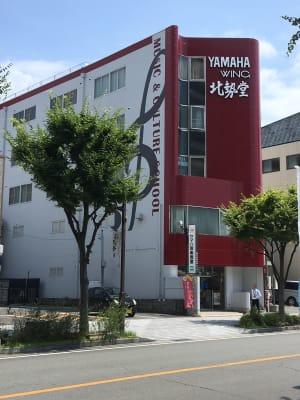 桑名駅から徒歩7分、駐車場30台、八間通りに面したワインカラーの5階建てのビルの3階にあります。 - ヤマハウイング北勢堂ビル内 多目的スペース ホールの外観の写真