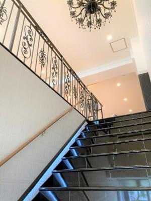 大理石の階段は各種撮影でのご利用に最適です。 真鍮の手すりや頭上のシャンデリアが非日常間を演出します。 - オダケイジダンスアカデミー ダンススタジオの室内の写真
