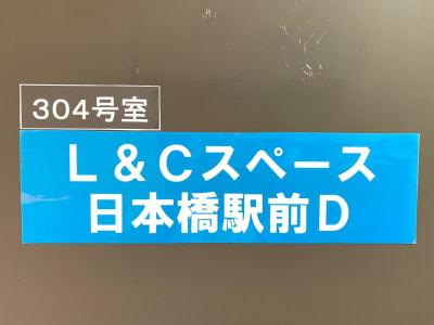 扉に看板を掲げています。ドアノブにキーボックスがあります。 - L&Cスペース日本橋駅前 D号室の入口の写真