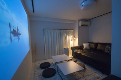 壁一面に写せるプロジェクター✨(110インチ相当) 大きめのソファでゆったり映画鑑賞はいかがでしょうか🎥 - FUN HOUR 心斎橋 パーティールームの室内の写真