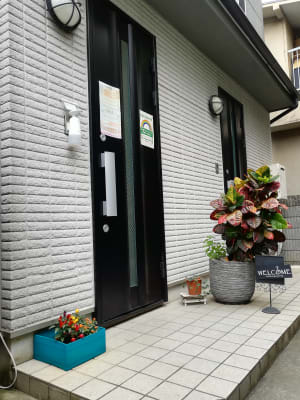 入口周辺にも、生花.観葉植物等生きたグリーンでお客様をお出迎え。 - レンタルサロン【NONO】 レンタルサロンの入口の写真