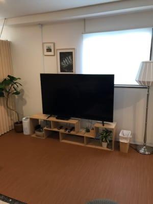 65型の大型テレビをご用意しています。VODも視聴可能です。 - RIVERSUITES 多目的スペース【3F】の室内の写真