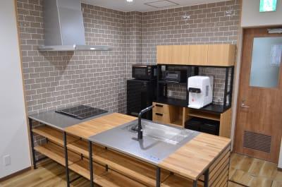 アイアンウッド調のアイランドキッチンが備わっています。 - コモンルーム中津 貸切レンタルスペースの室内の写真
