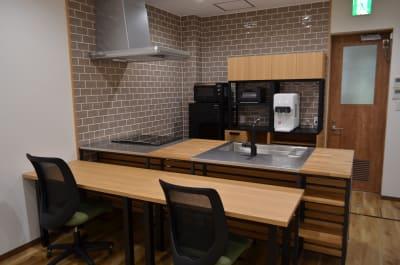 キッチン側に机を配置し、バーのようなレイアウトも可能です。 - コモンルーム中津 貸切レンタルスペースの室内の写真