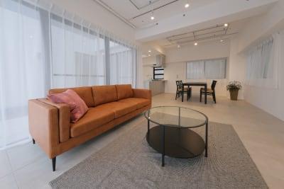 【Room1】6.7m x 3.4m ●タイル床に漆喰壁、オールステンレスのキッチン(3口コンロ)と大型冷蔵庫を設置。グラスやお皿、カトラリーなどもご用意しています。 ●さらに4人掛けのテーブルと3人掛けのソファもご用意。 ●吹き抜けのバルコニーもありとても開放感があります。 ●窓には遮光カーテンも設置。 - Well Studio 千駄ヶ谷 キッチン・バルコニー付きスタジオの室内の写真