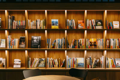ラウンジの本棚には旅に関する本が沢山! - WeBase 京都  コワーキングスペースの室内の写真