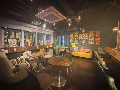 アート例。木のぬくもりとカラフルな家具でアーティスティックな店内。紺色の壁紙が絵を際立たせます。  - gallery EMONS ギャラリー、個展、ライブの室内の写真