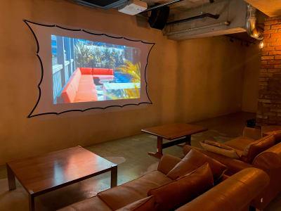 地下1階:試写会やセミナー用のプロジェクター完備 アンティークなソファーもご利用くださいませ - A YOTSUYA 【撮影】地下1階イベントスペースの室内の写真