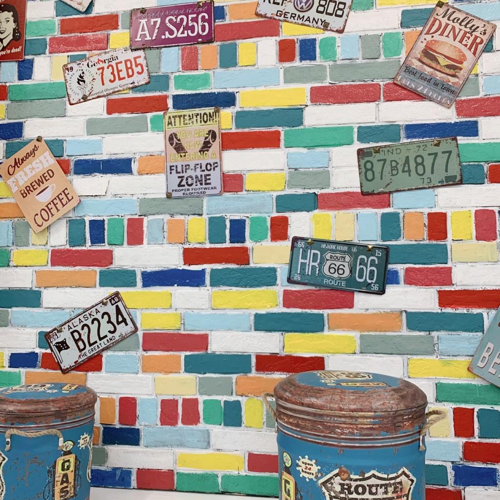 レンガにカラフルなペンキを塗ったポップな壁にブリキ看板でレトロアメリカンを演出。 - スタジオ羅寂RAJAQの室内の写真
