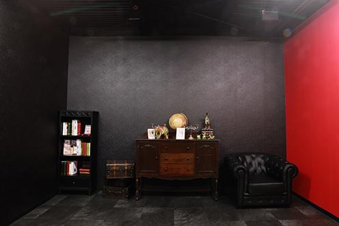 黒を基調にしたゴシックな雰囲気のお部屋です。アンティークの家具を多数ご用意しております。また、一面だけ壁を赤色にしておりますので、雰囲気を変えた撮影も可能です。 - ココスタジオ 黒・グレー2種類の撮影ルームの室内の写真